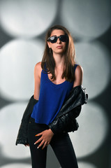trendy young woman with sunglasses posing in the studio