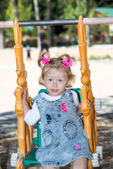 Happy adorable child girl on swing on playground