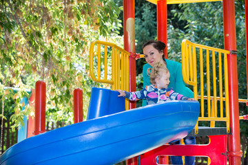 Happy adorable girl with mom on children's slide on playground