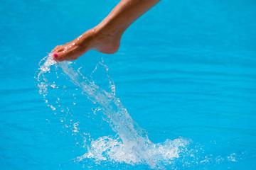 girl's beauty legs in the pool making splashes