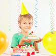 Little kid in holiday hat with a piece of birthday cake