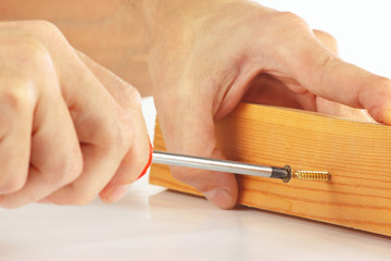 Hand of repairman tightening the screw into the wooden block