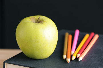 Apple on pile of books and pencils