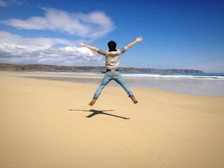Young man form behind jumping in an empty beach
