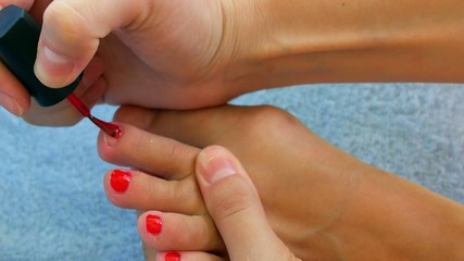 Female Polishing Foot Nails with Red Nail Polish. Pedicure.
