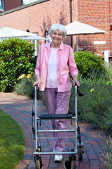 Happy elderly woman using a walking aid.