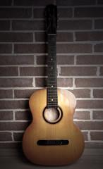 Guitar on floor on brick wall background