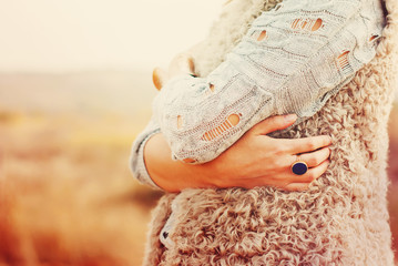 Woman Embraces Herself Hands, Ring in the finger