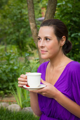 Beautiful young woman drinking coffee outdoors
