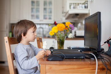 Adorable little boy, having lollipop while watching cartoon
