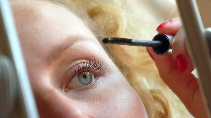 Closeup of Woman Applying Mascara in Mirror at Home.