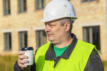 Construction Engineer with cup of coffee near building