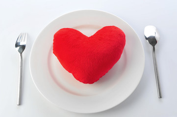 Red heart in plate with fork and spoon