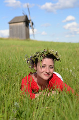 Preety lady with wreath laying in green meadow