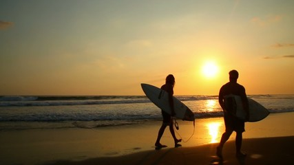 Two surfers walk at sunset on the beach