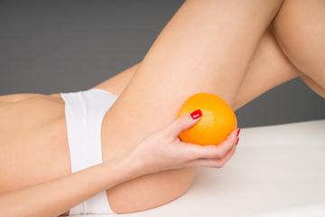 Frau mit einer Orange in der Hand