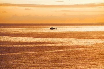 Vessel is sailing in the ocean at sunrise