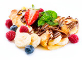 Fototapety Crepes with banana, chocolate and berries over white