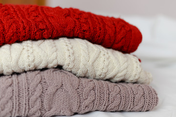 image of hand made knitted sweaters three colored in pile