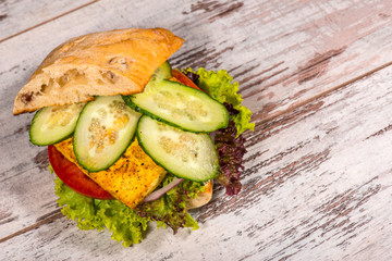 Close-up picture of vegetarian sandwich with tofu, tomatoes, sal