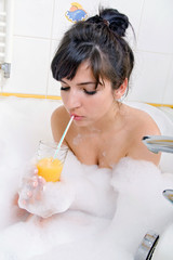 Young brunette woman with juice in the bathtub