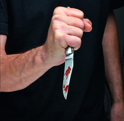 Man with a bloody knife in a hand. Closeup