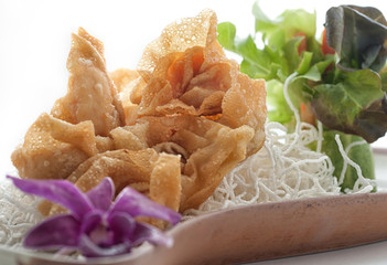 Fried dough with crispy noodles in brown plate