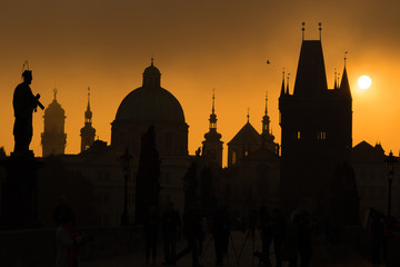 Silhouettes of Prague towers and statues on Charles bridge durin
