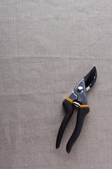 Garden scissors on a gray fabric
