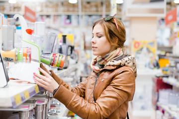 Housewife choosing grinder at the supermarket