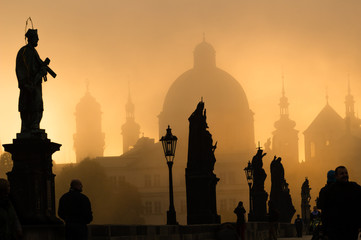 Silhouette of statue and tourists on Charles bridge during sunri