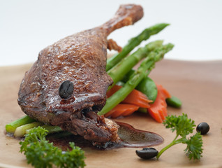 Fried duck leg with morning glory on brown plate.