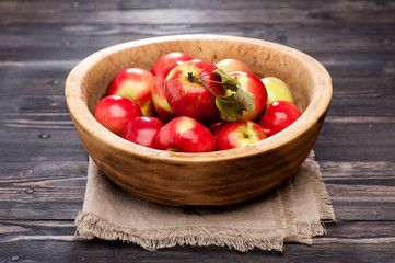 Ripe red apples in wooden bowl