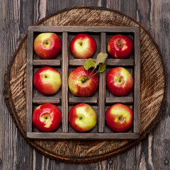 Red apples in wooden box. Collage.