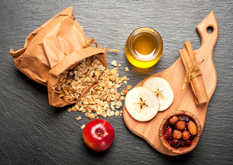 Granola honey, apples, dried berries on dark background
