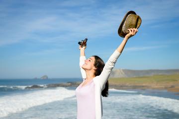 Blissful woman raising arms towards the sea
