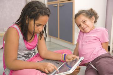 2 jeunes filles jouant à la tablette dans la chambre