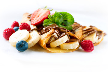 Crepes with banana, chocolate and berries closeup