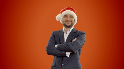 young businessman in hat of Santa Claus on orange background