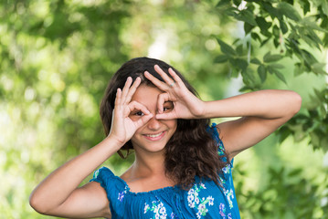 Teen girl showing sign  on  nature