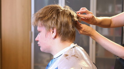 the hairdresser does a hairstyle to the client - young man