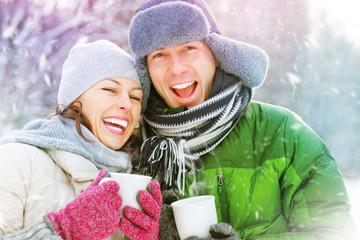 Happy winter couple having fun outdoors. Hot drinks
