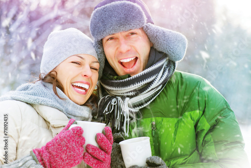Leinwandbild Motiv Happy winter couple having fun outdoors. Hot drinks