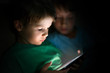 Little boys playing on tablet at night