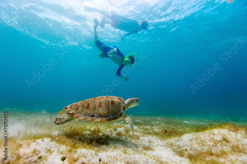 Tuinposter Duiken Family snorkeling with sea turtle