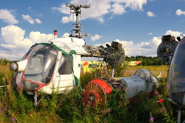 Old airplane fuselage and rusty helicopters on green grass