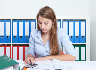 Studentin am Schreibtisch arbeitet mit Taschenrechner