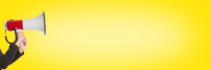 Geschäftsfrau mit Megafon vor Gelb