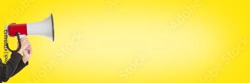 canvas print picture Geschäftsfrau mit Megafon vor Gelb