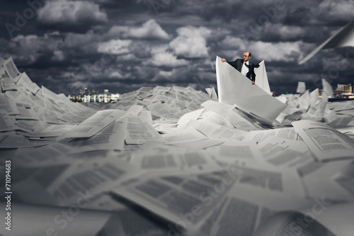 Successful businessman sailing on paper boat - 71094683